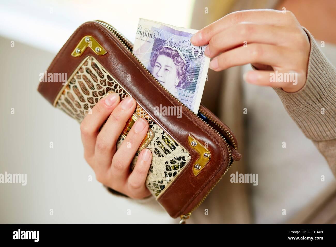 Femme prenant de l'argent de son sac à main Banque D'Images
