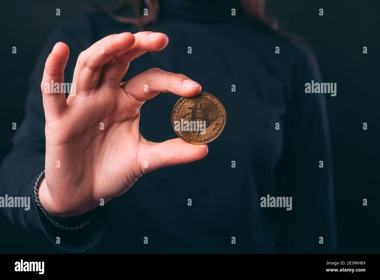 Les mains des femmes tiennent une pièce de monnaie en bitcoin sur fond noir. Banque D'Images