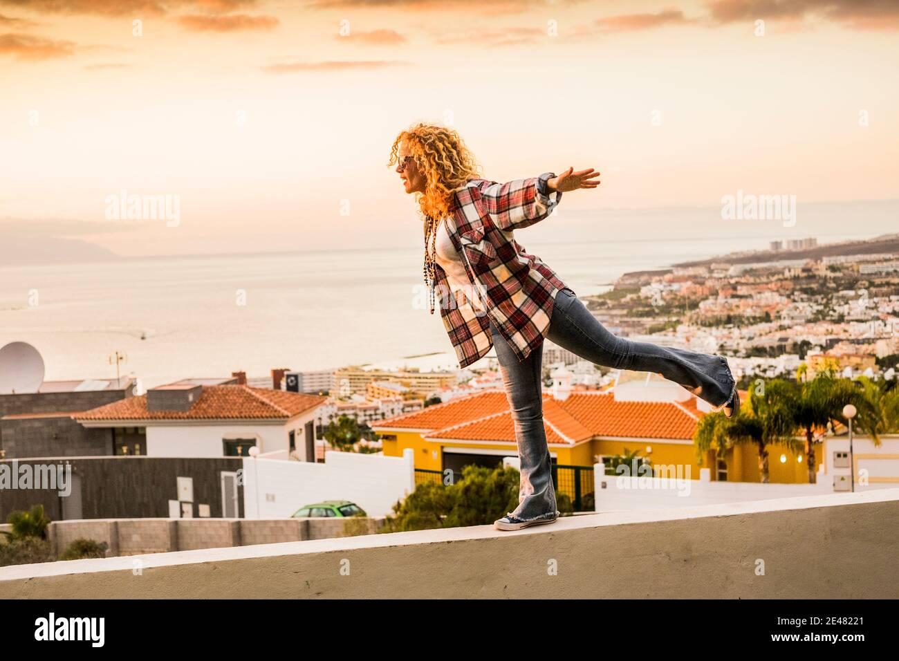 Concept de bonheur et de liberté pour une jeune femme indépendante et belle marchant équilibré sur un mur avec la ville et la côte de mer dedans contexte - vacances d'été Banque D'Images