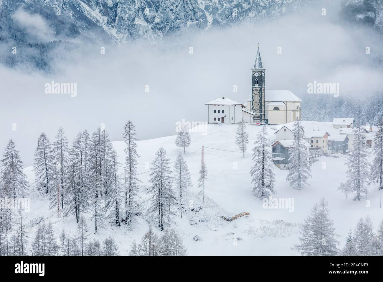 Italie, Vénétie, province de Belluno, Rocca Pietore, Agordino, le village de Laste en hiver avec l'église de San Gottardo sur la colline, Dolomites Banque D'Images