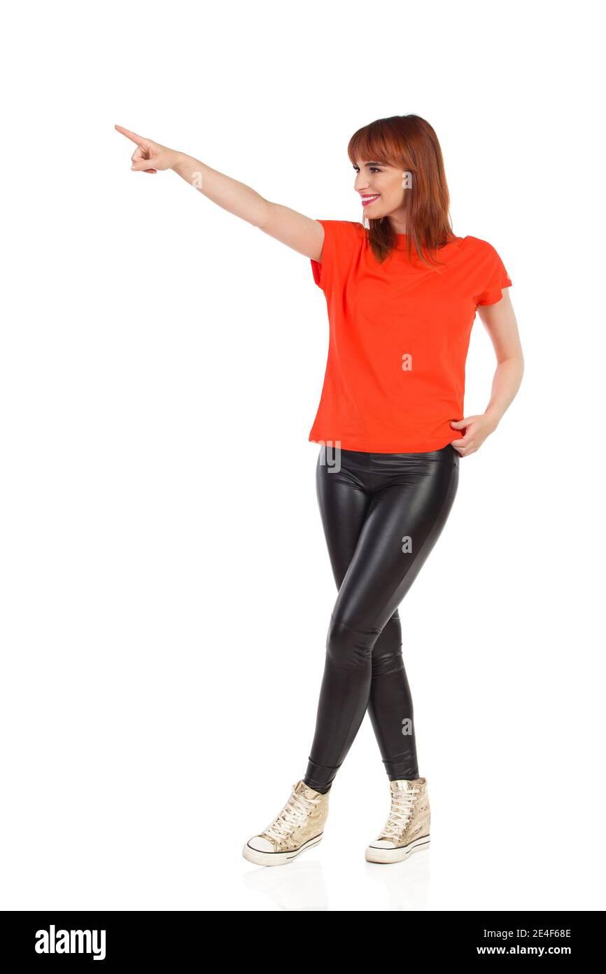 Une jeune femme souriante se tient debout avec les jambes croisées, regardant loin et pointant. Prise de vue en studio sur toute la longueur isolée sur blanc. Banque D'Images
