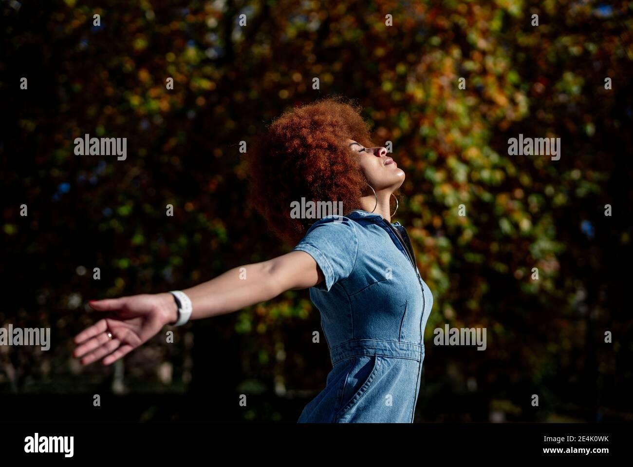 Femme adulte de taille moyenne avec bras étirés et yeux fermés à parc public Banque D'Images