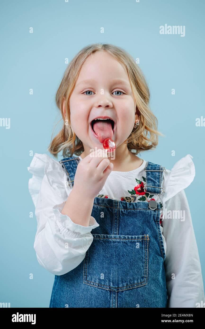 Bonne petite fille blonde aime manger des bonbon de Lollipop sur bleu Banque D'Images