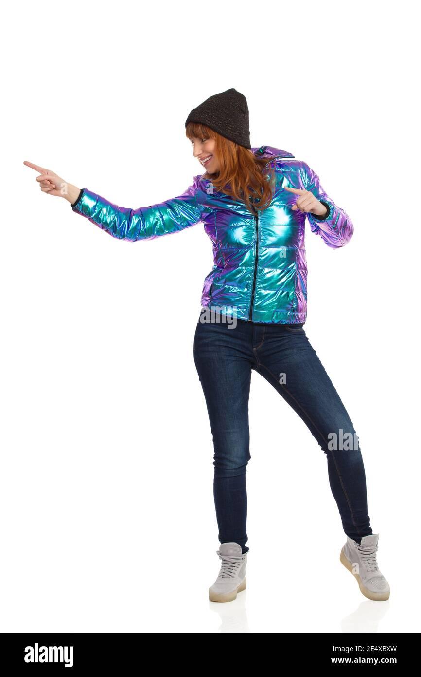 Bonne jeune femme en duvet, casquette, jeans et baskets brillants et éclatants, regarde loin et touche quelque chose avec l'index. Goujon sur toute la longueur Banque D'Images