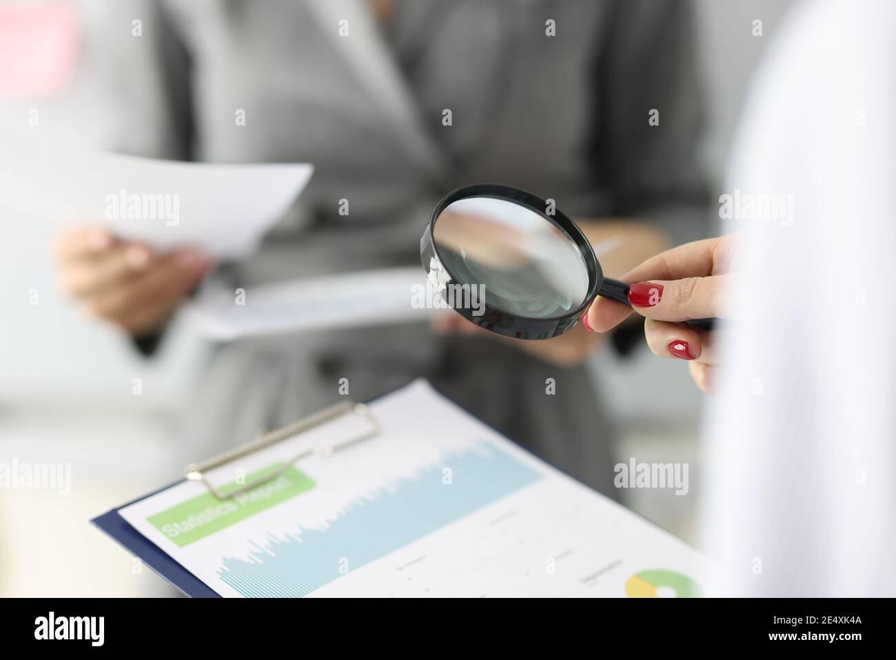 La main femelle tient une loupe et un presse-papiers avec des chiffres financiers Banque D'Images