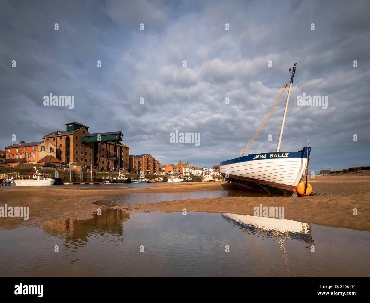Bateau à ramer en bois sur les rives de sable du port de Wells. Banque D'Images