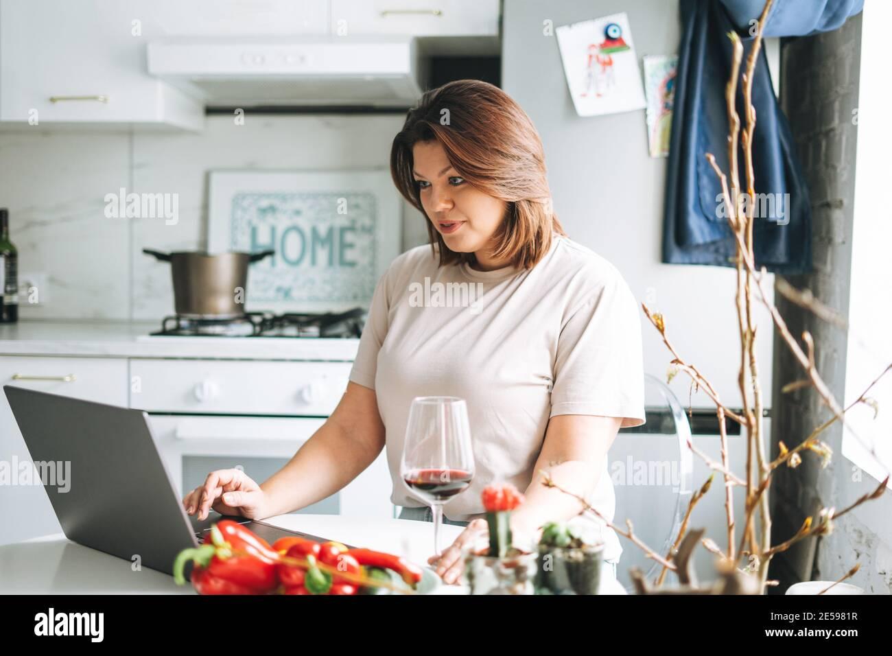 Belle brunette souriante jeune femme plus taille corps positif en utilisant ordinateur portable dans la cuisine à la maison Banque D'Images
