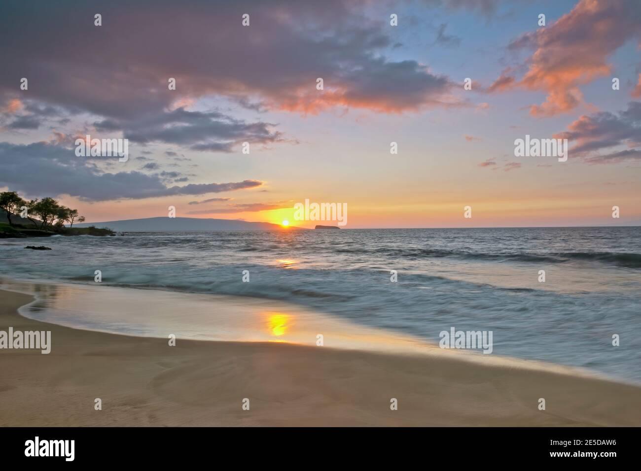 Coucher de soleil derrière les îles de Kahoolawe et Molokini au large de la plage de Makena, sur l'île de Maui à Hawaï. Banque D'Images