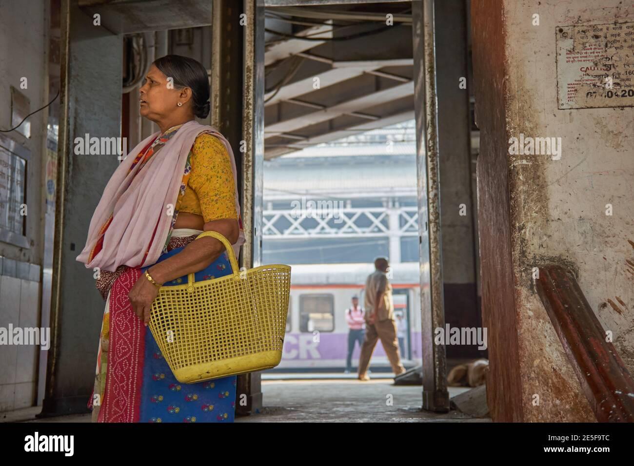 Après avoir débarqué d'un train de banlieue, une femme au foyer de Mumbai quitte Chhatrapati Shivaji Maharaj Terminus à Mumbai, la gare la plus fréquentée de la ville Banque D'Images