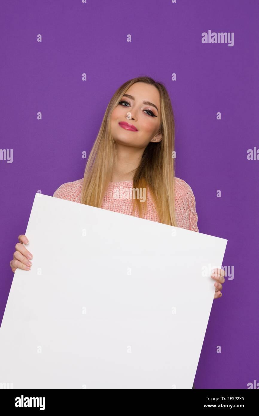 Jeune femme gaie dans le chandail rose tient blanc grande affiche vide. Vue avant. Taille haute, prise en studio sur fond violet. Banque D'Images