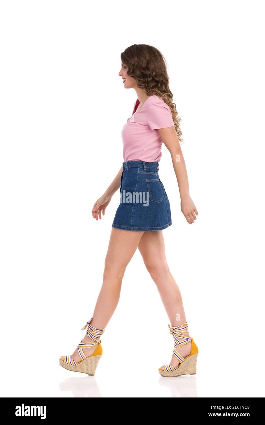 Marche jeune femme en Jean mini jupe, haut rose et chaussures à talons compensés. Vue latérale. Prise de vue en studio sur toute la longueur isolée sur blanc. Banque D'Images
