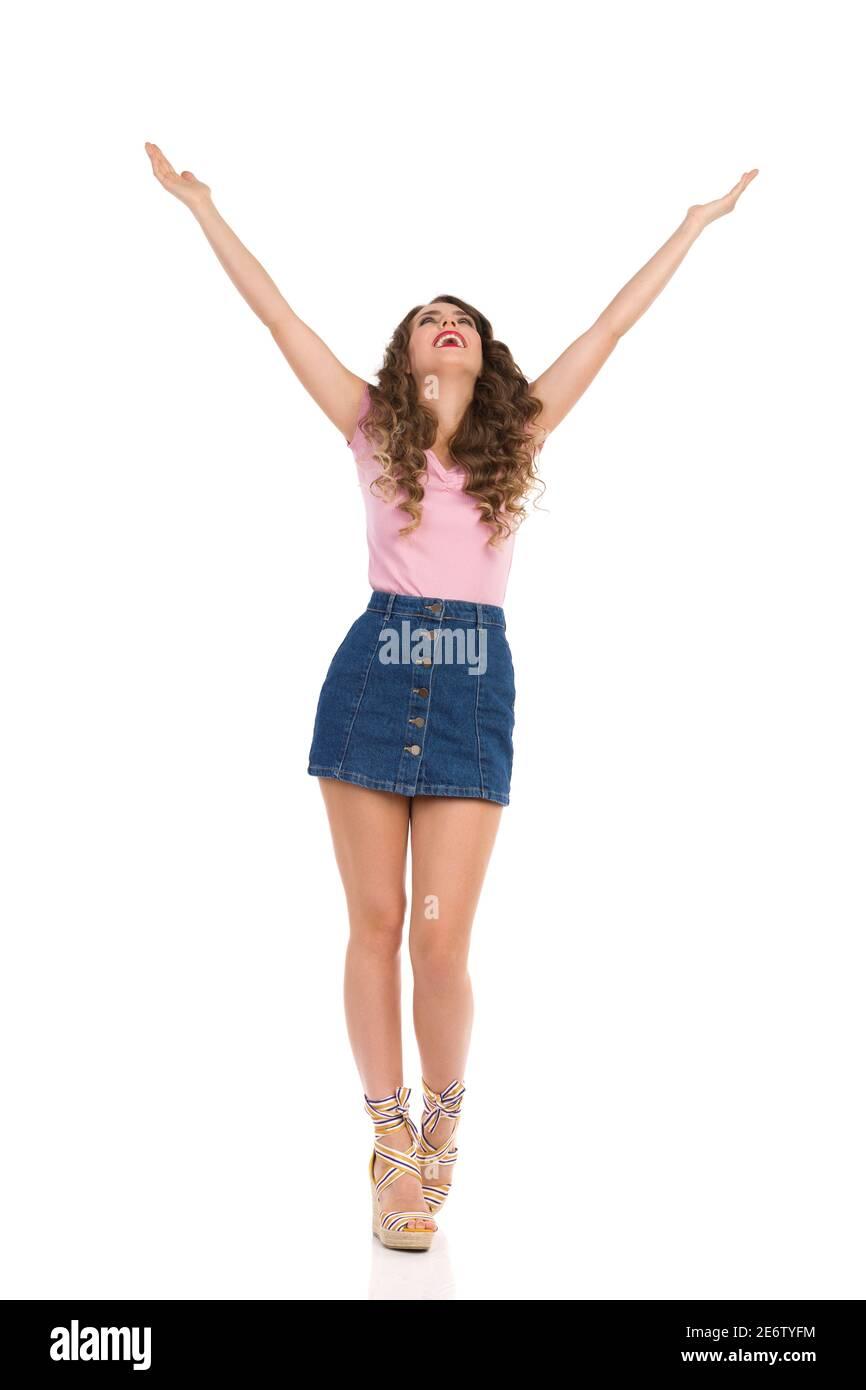 Bonne jeune femme en Jean mini jupe, le haut rose et les chaussures à talons compensés est debout avec les bras étirés et regardant vers le haut. Vue avant. Prise de vue en studio Banque D'Images