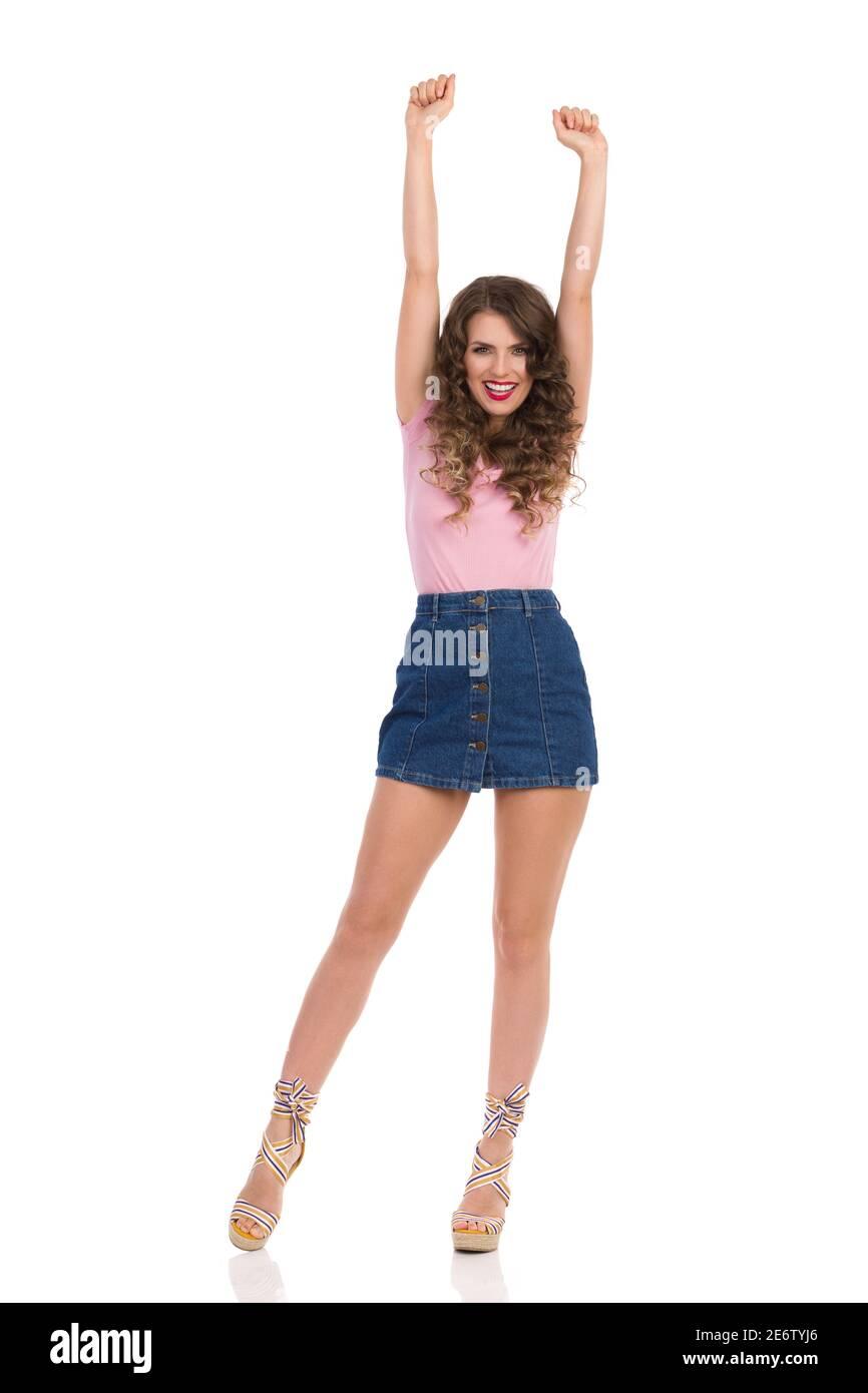 Bonne jeune femme en Jean mini jupe, le haut rose et les chaussures compensées est debout avec les bras relevés et applaudissent. Vue avant. Isolation de la prise de vue en studio pleine longueur Banque D'Images