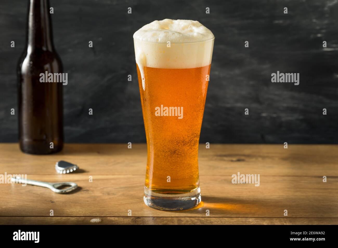 Bière dorée dans un grand verre avec mousse Banque D'Images