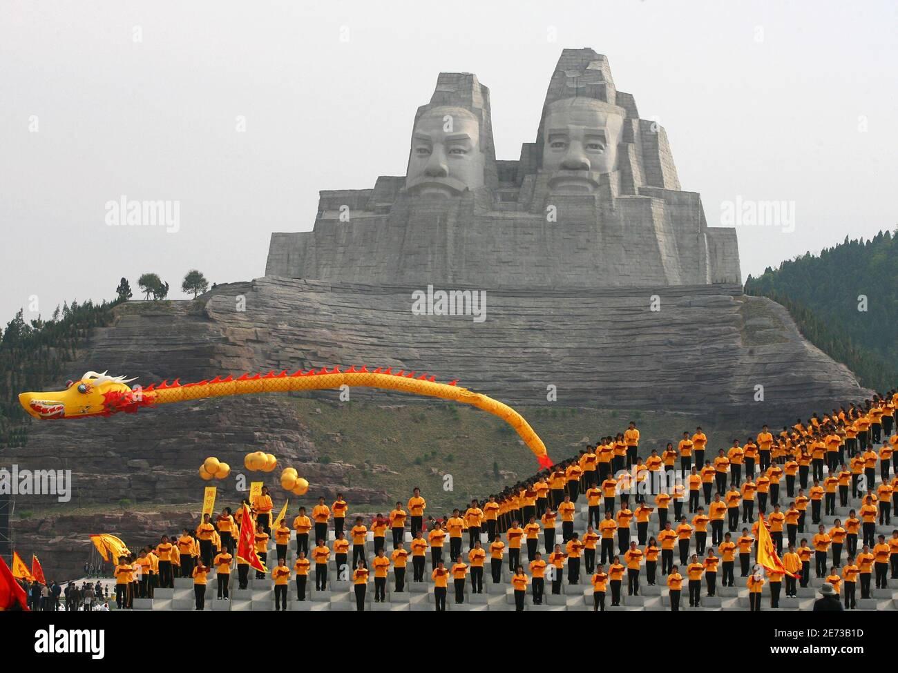 Les gens se présentent lors d'une répétition devant les statues de Huang Di et de Yan Di, qui sont vénérés comme les ancêtres communs du peuple chinois, à Zhengzhou, dans la province du Henan en Chine centrale le 16 avril 2007. La cérémonie d'achèvement des statues, qui ont une hauteur d'environ 106 mètres (348 pieds) et ont coûté 180 millions de yuans (23 millions de dollars), aura lieu mercredi, selon les médias locaux. REUTERS/Donald Chan (CHINE) Banque D'Images