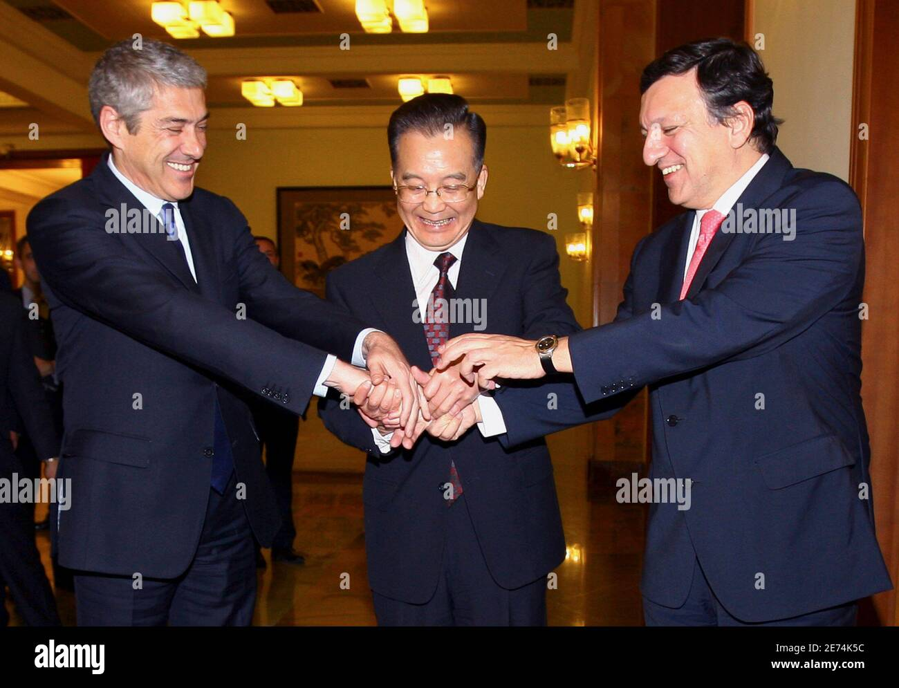 Portugal's Prime Minister and European Union President Jose Socrates (L) and European Commission President Jose Manuel Barroso (R) laugh as China's Premier Wen Jiabao (C) holds their hands together before their meeting in the Great Hall of the People in Beijing November 28, 2007.         REUTERS/David Gray    (CHINA) Banque D'Images