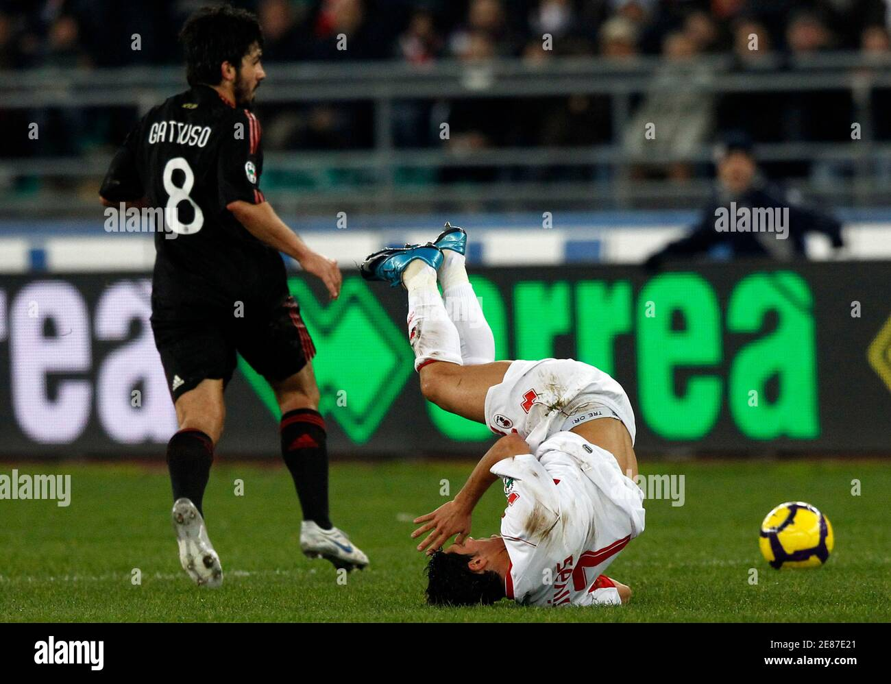 Bari's Emanuel Benito Rivas (R) flies down as  Gennaro Gattuso (C) of AC Milan passes near during their Serie A soccer match at the San Nicola stadium in Bari February 21, 2010.  REUTERS/Alessandro Bianchi   (ITALY - Tags: SPORT SOCCER) Banque D'Images