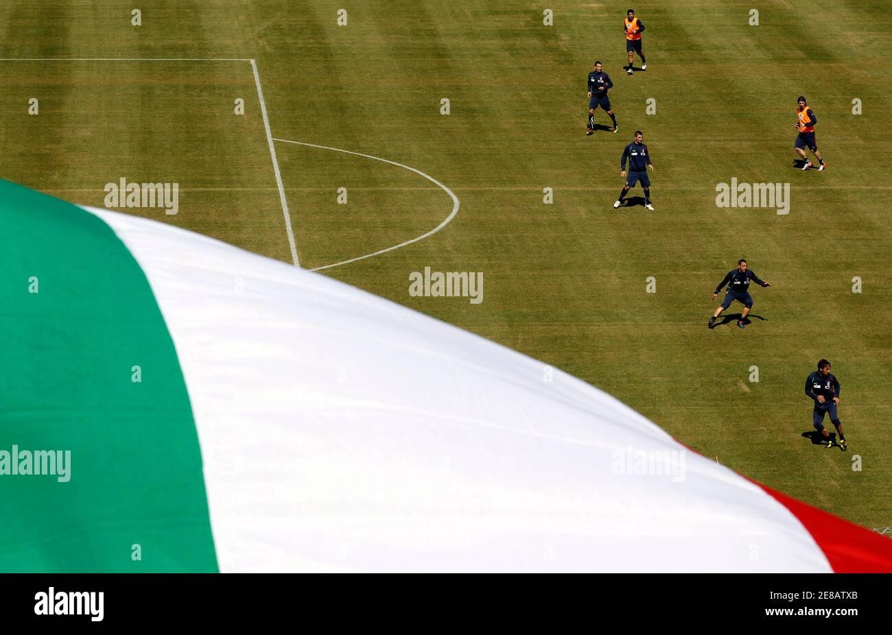 Un drapeau national italien vole alors que les joueurs de football italiens s'exercent lors d'une séance d'entraînement matinale à Sestriere le 24 mai 2010. REUTERS/Alessandro Bianchi (ITALIE - TAGS: SPORT FOOTBALL COUPE DU MONDE IMAGES DU JOUR) Banque D'Images