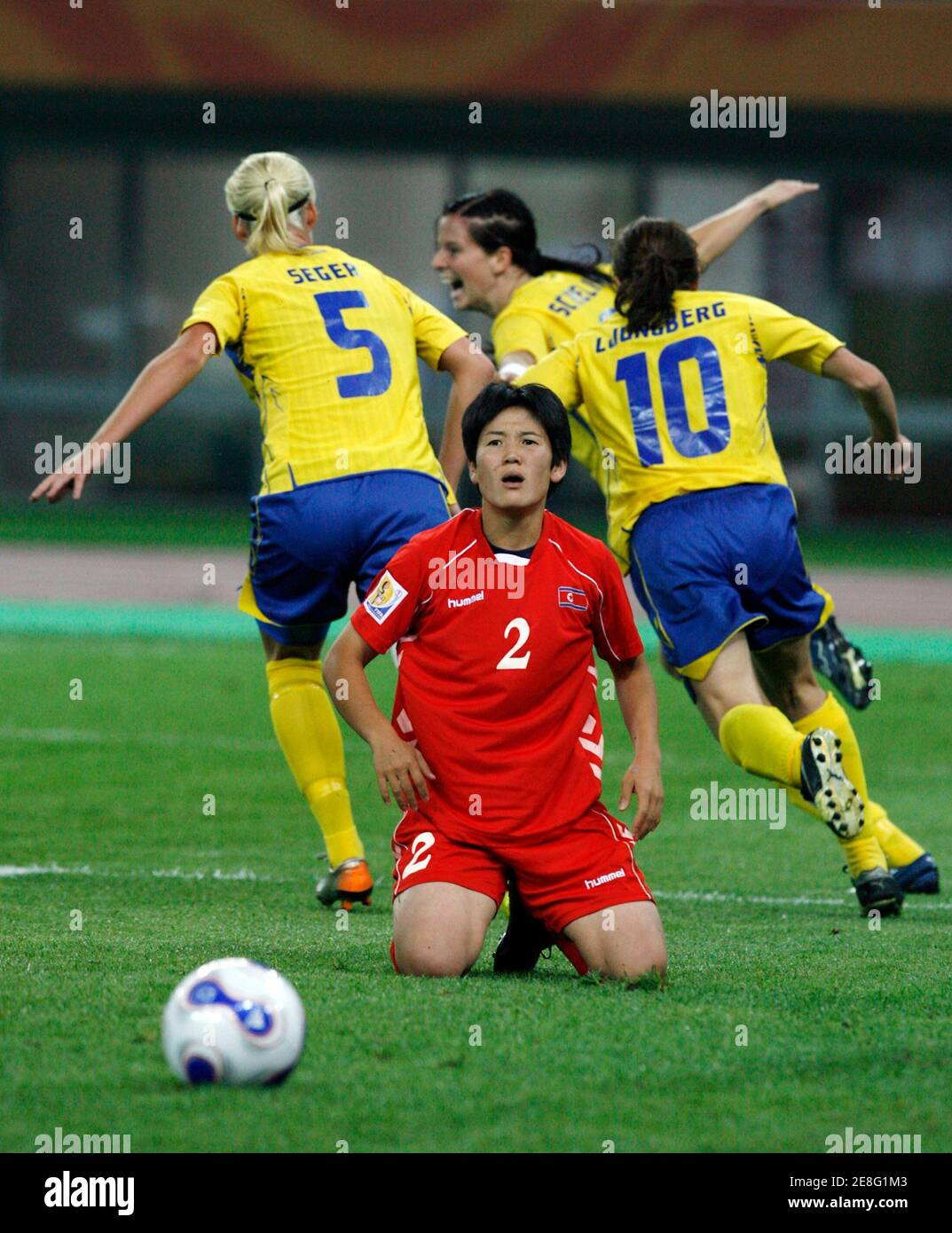 North Korea's Kim Kyong Hwa (2) reacts as Sweden's players celebrate after Charlotta Schelin (C, back) scores, chased by team mates Caroline Seger (5) and Hanna Ljungberg (10) during their Group B soccer match at the 2007 FIFA Women's World Cup in Tianjin September 18, 2007.    REUTERS/Claro Cortes IV   (CHINA) Banque D'Images