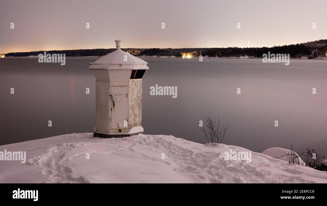 Phare blanc sur la côte de Bogesundslandet en direction de Lidingö, en Suède, près de Stockholm, pendant une nuit d'hiver Banque D'Images