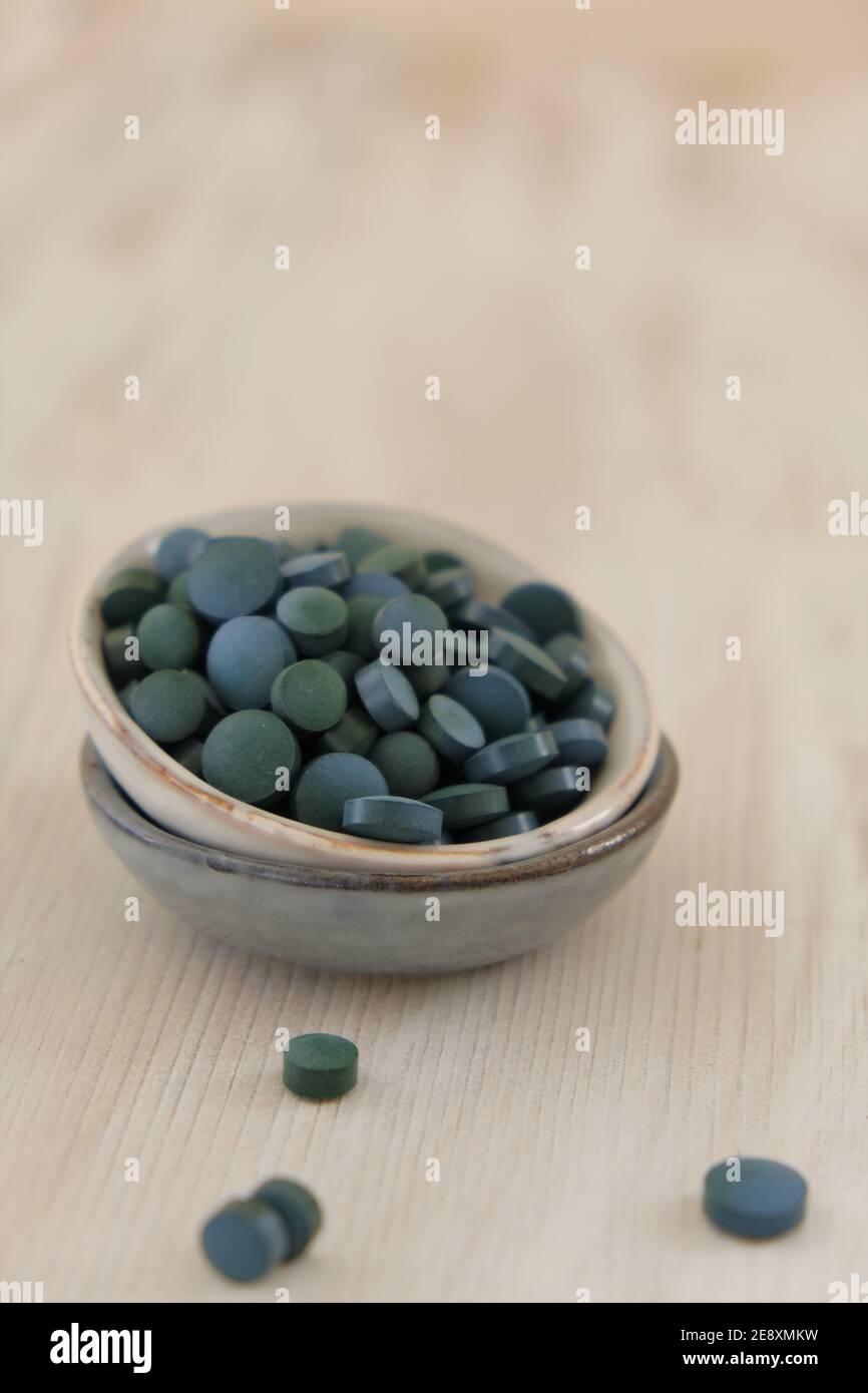 Spiruline algue vert en comprimés dans des tasses rondes en céramique sur un fond en bois clair..Suppléments diététiques.Super nourriture. Algue biologique saine.saine Banque D'Images