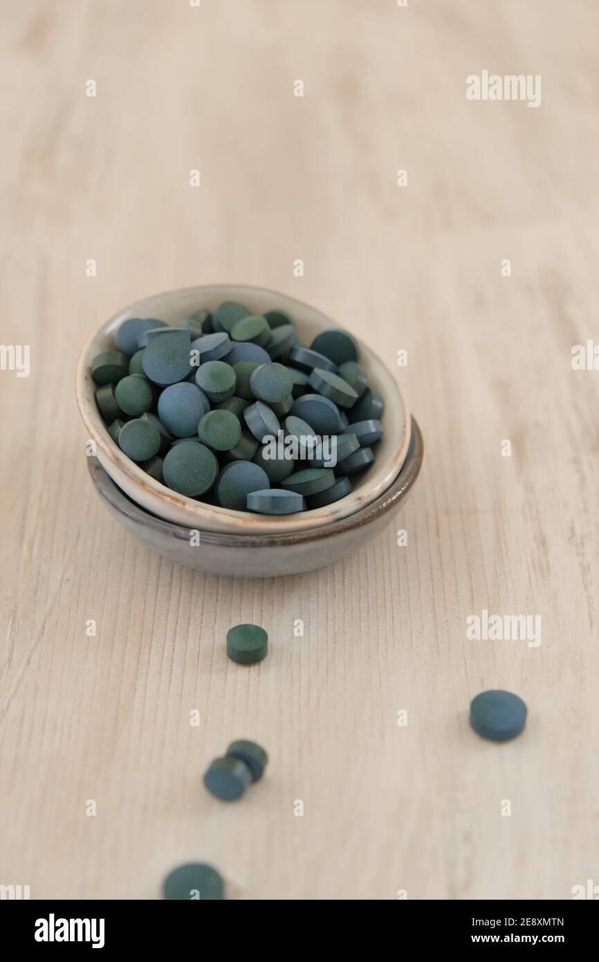 Spiruline algue vert en comprimés dans des tasses rondes en céramique sur un fond de merde en bois..Suppléments diététiques.Super nourriture. Algue biologique saine.saine Banque D'Images
