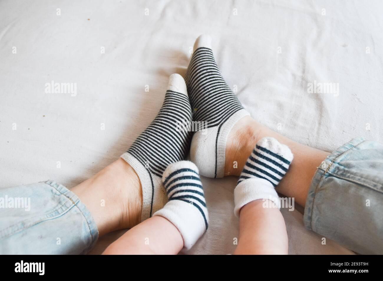 Les pieds de la mère et du bébé avec des chaussettes assorties Banque D'Images