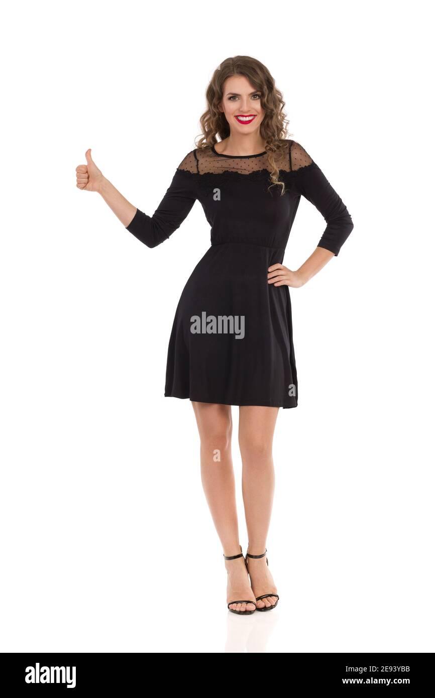 Élégante jeune femme en noir cocktail mini robe et talons hauts montre le pouce vers le haut et sourire. Vue avant. Prise de vue en studio sur toute la longueur isolée sur blanc Banque D'Images