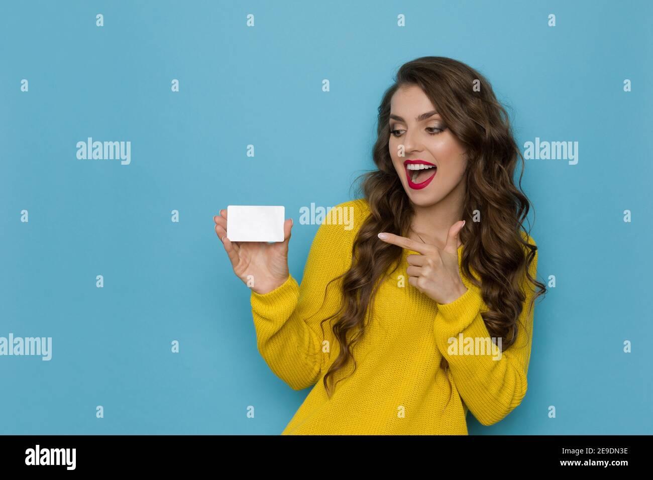 Une jeune femme excitée et heureuse en chandail jaune tient une carte en plastique blanc, pointant vers elle et parlant. Taille haute studio tourné sur fond bleu. Banque D'Images