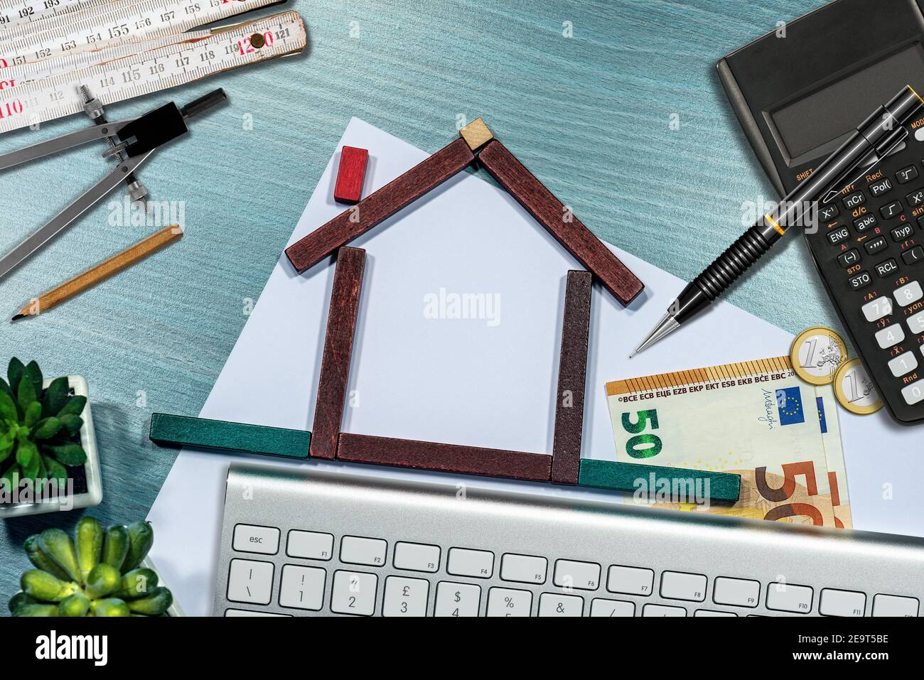 Petite maison en bois faite de blocs de jouets sur le bureau, avec euro monnaie, calculatrice, règle pliante. Concept d'investissements immobiliers. Banque D'Images