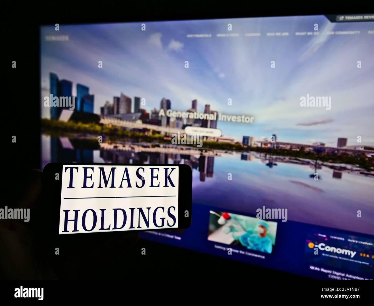 Personne tenant un smartphone avec le logo de la société d'investissement Singapourienne Temasek Holdings sur l'écran devant le site Web. Mise au point sur l'affichage du téléphone. Banque D'Images