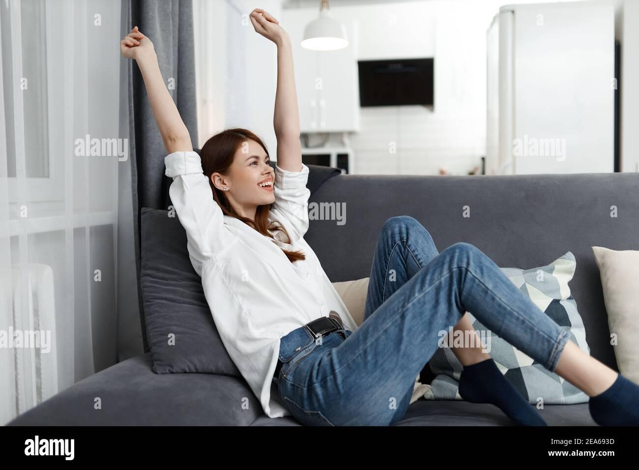 femme assise avec les mains levées vers le haut sur le canapé appartement à temps libre Banque D'Images