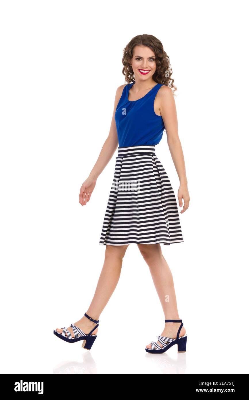 Jeune femme souriante en jupe rayée, talons hauts et bleu haut est de marche et regarder l'appareil photo. Vue latérale. Prise de vue en studio sur toute la longueur isolée sur blanc. Banque D'Images