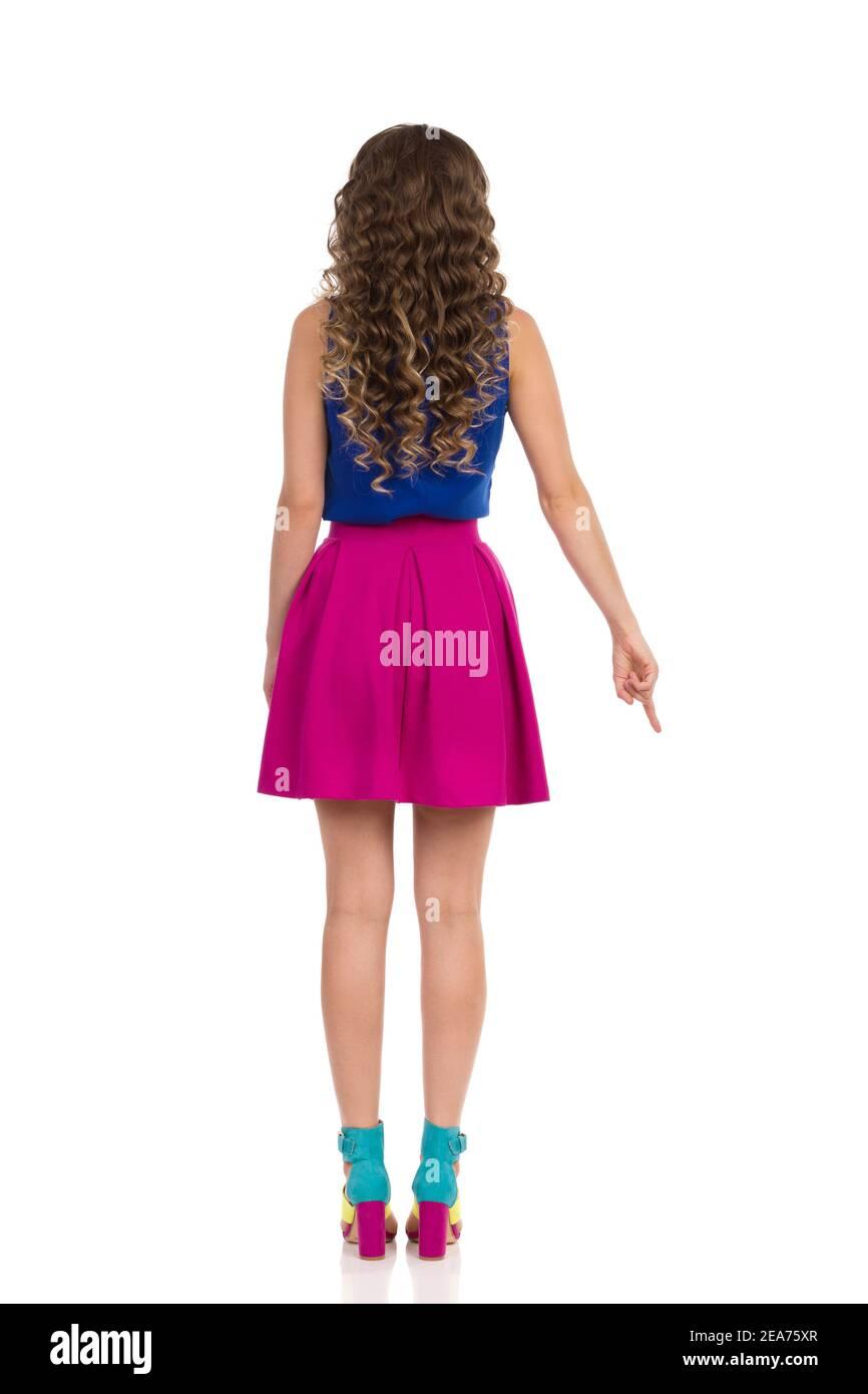 Belle jeune femme en hauts talons hauts colorés, mini jupe rose et bleu haut est debout et pointant vers le bas. Vue arrière. Prise de vue en studio pleine longueur isolée Banque D'Images