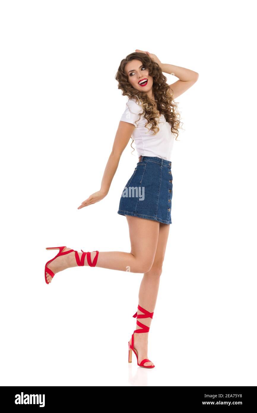 Insouciante et heureuse jeune femme en Jean mini jupe, blanc haut et rouge talons hauts est dancig sur une jambe et crier. Prise de vue en studio pleine longueur isolée o Banque D'Images