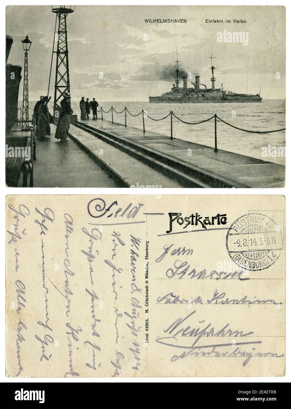 Carte postale historique allemande : jetée à l'entrée du port de Wilhelmshaven. Les femmes et les hommes regardent le navire de guerre. Guerre mondiale un 1914-1918 Banque D'Images