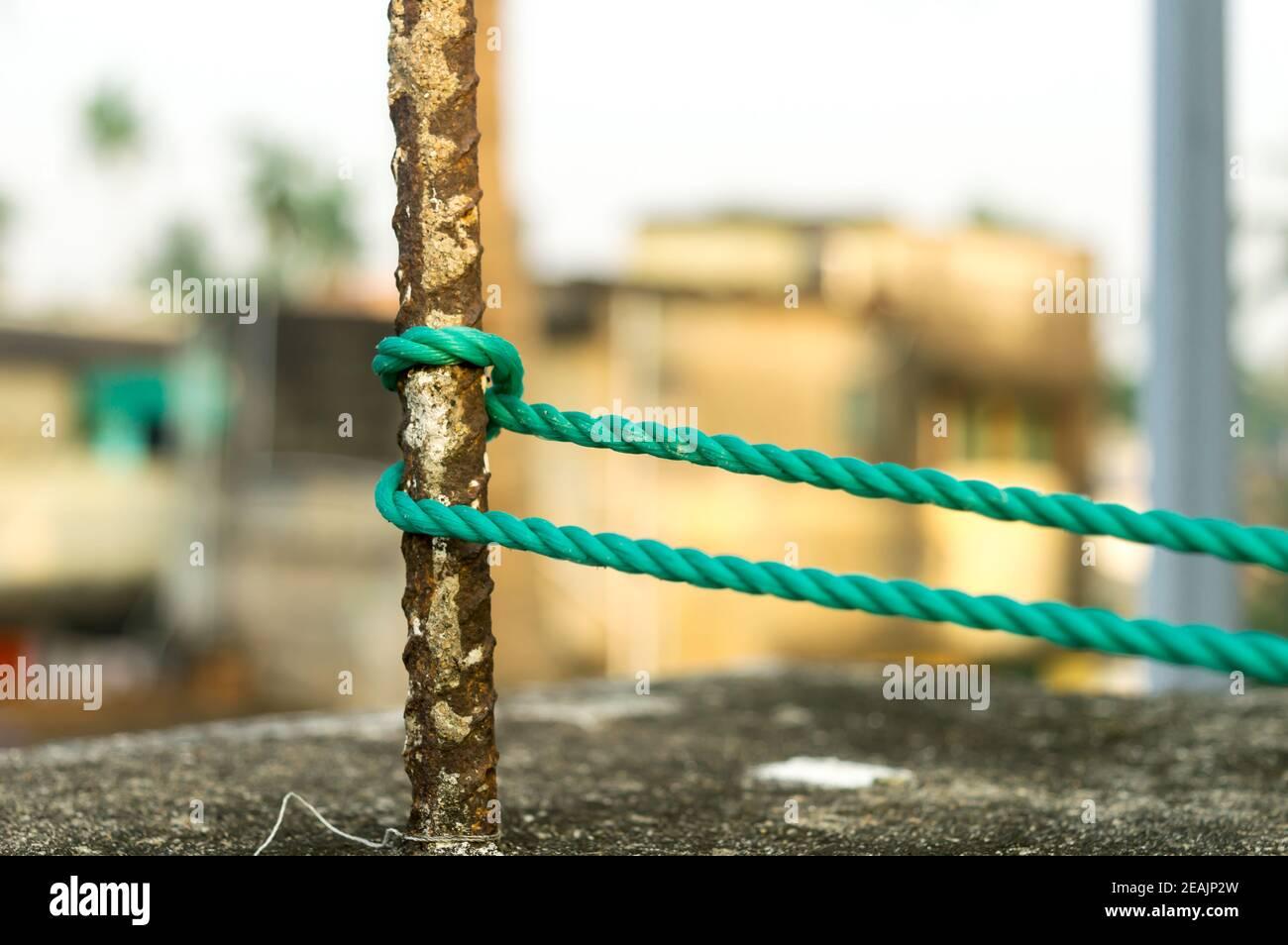 Une corde est attachée dans un nœud autour d'un poteau de clôture, corde attachée nœuds d'attelage sur un poteau de fer rouillé isolé de l'arrière-plan. Banque D'Images