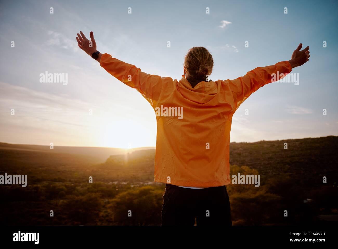 Vue arrière d'un jeune homme debout sur la montagne avec étiré les bras se détendus après une course matinale dans la nature Banque D'Images