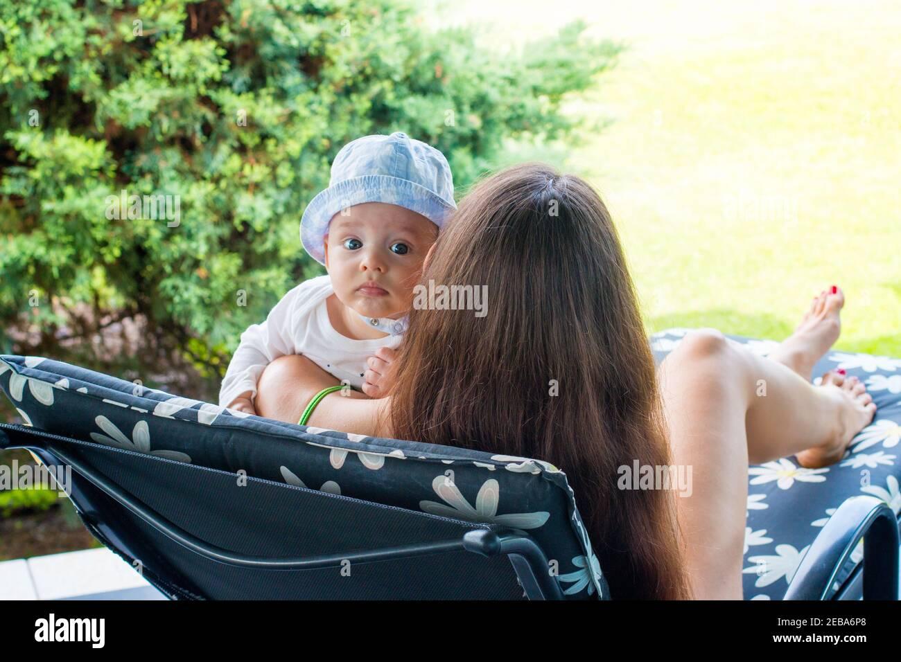 Enfant dans les bras de la mère, nouvelle mère reposant avec un bébé de 5 mois sur une chaise longue Banque D'Images