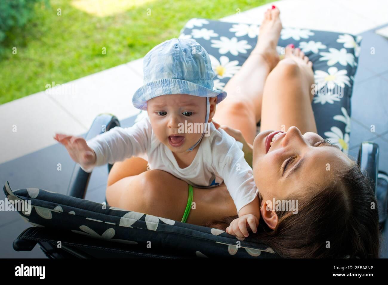 Jolie maman aimante essayant d'apaiser le bébé rouge cramoisi et de se débarrasser de la peur de bébé en la tenant dans les bras de mère, en embrassant et en souriant avec joie Banque D'Images