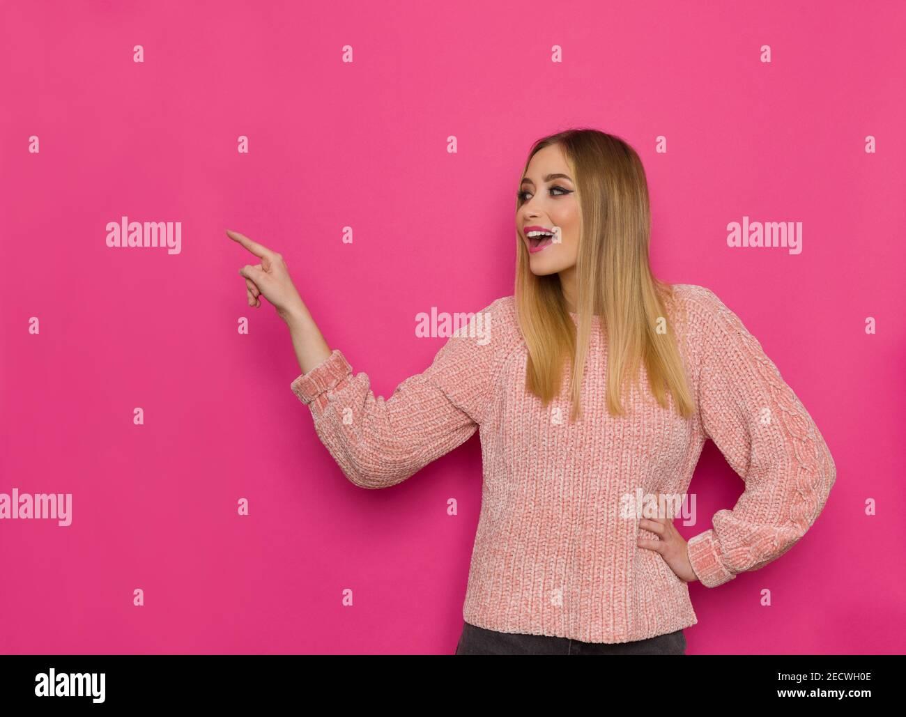 Une jeune femme excitée en chandail rose regarde loin et essaie de toucher quelque chose avec l'index et de parler. Taille haute studio tourné sur fond rose Banque D'Images