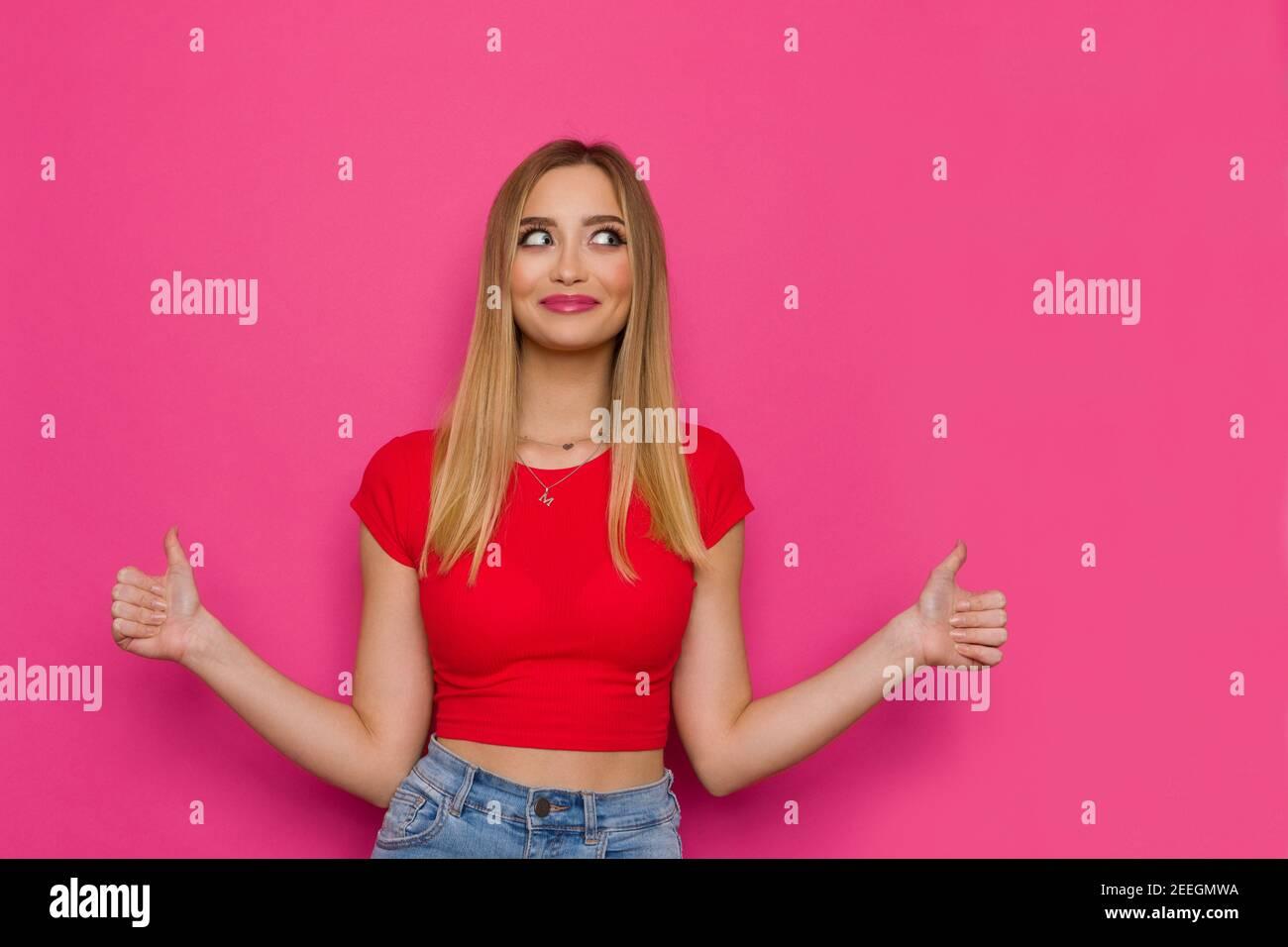 Mignon décontracté jeune femme en haut rouge montre les pouces vers le haut et regarde le côté. Taille haute studio tourné sur fond rose. Banque D'Images