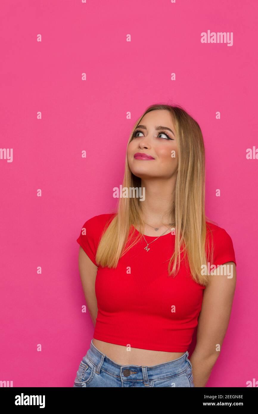 Curieuse jeune femme en haut rouge tient les mains derrière, regardant vers le haut et souriant. Taille haute studio tourné sur fond rose. Banque D'Images