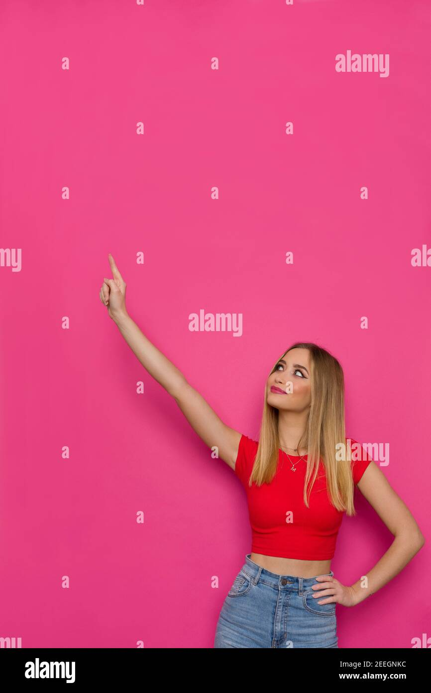 Belle jeune femme en haut rouge tient le bras relevé, regardant loin et pointant vers le haut. Taille haute studio tourné sur fond rose. Banque D'Images
