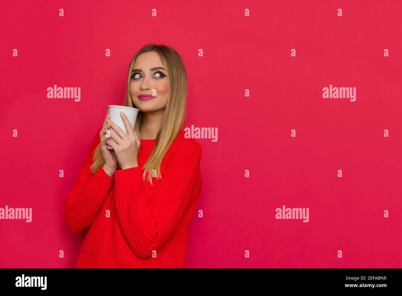Jolie jeune femme en chandail rouge tient une tasse blanche, regardant l'espace de copie et souriant. Taille haute studio tourné sur fond rouge. Banque D'Images