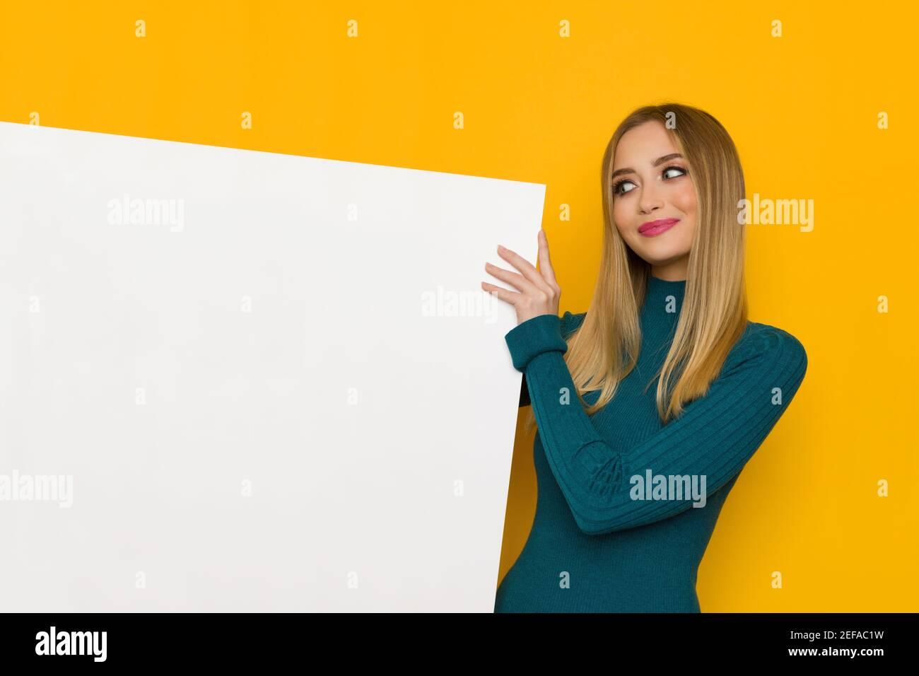 Jolie jeune femme souriante tient un écriteau blanc et regarde-le. Taille haute studio tourné sur fond jaune. Banque D'Images