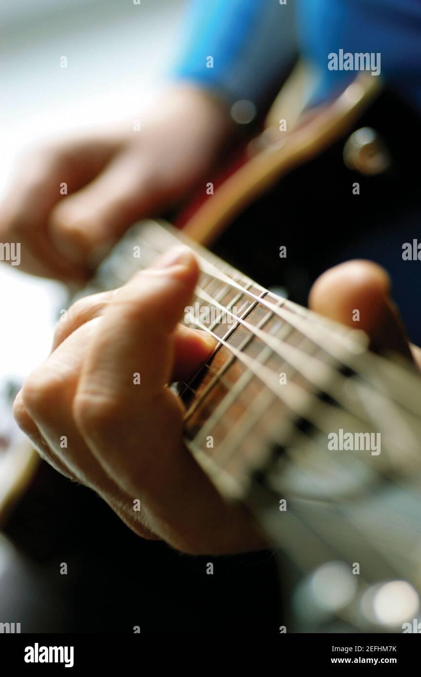Gros plan de l'homme jouant de la guitare acoustique Banque D'Images