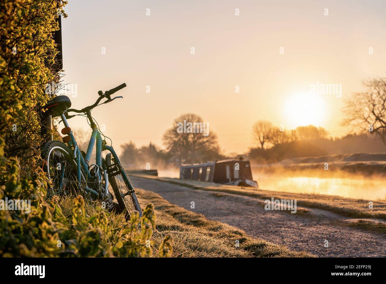 Bateau sur le canal avec VTT à gauche contre la haie lever du soleil tôt le matin à l'aube avec lumière dorée dans le ciel La rivière Trent et la brume se levant Banque D'Images
