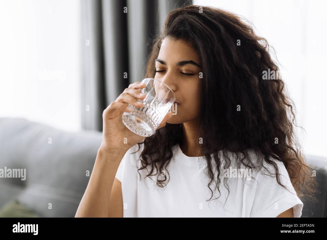 Un mode de vie sain. La jeune femme afro-américaine boit un verre d'eau tout en étant assise sur le canapé à la maison. Belle femme en bonne santé suivre un mode de vie sain Banque D'Images