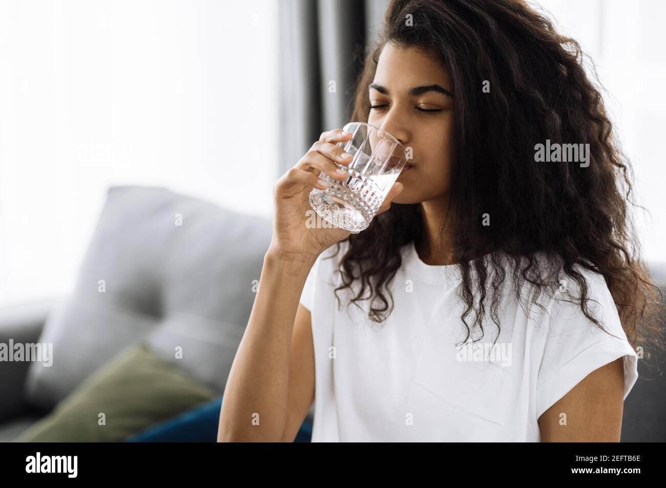 Belle fille suivre un mode de vie sain, boire une eau pure. Une femme afro-américaine boit quotidiennement de l'eau propre, concept de mode de vie sain Banque D'Images